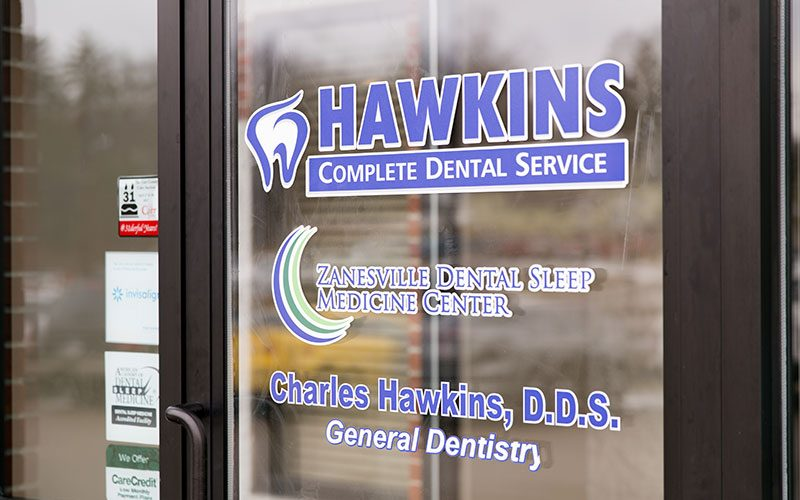 Signage On The Main Entrance Door of Hawkins Complete Dental Service in Zanesville, OH